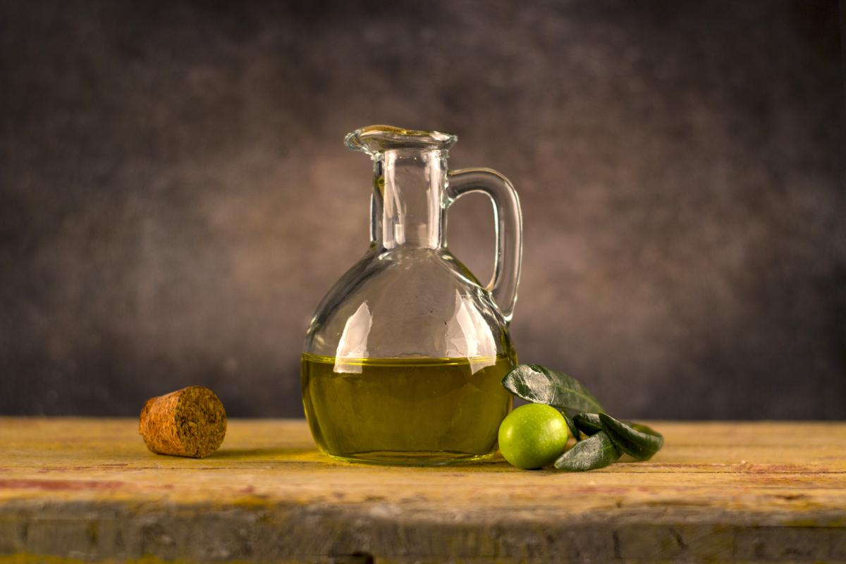 Still life painting of Olive Oil in glass jug with cork and green olive.